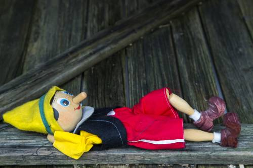 Wooden Pinocchio puppet splayed out on a bench